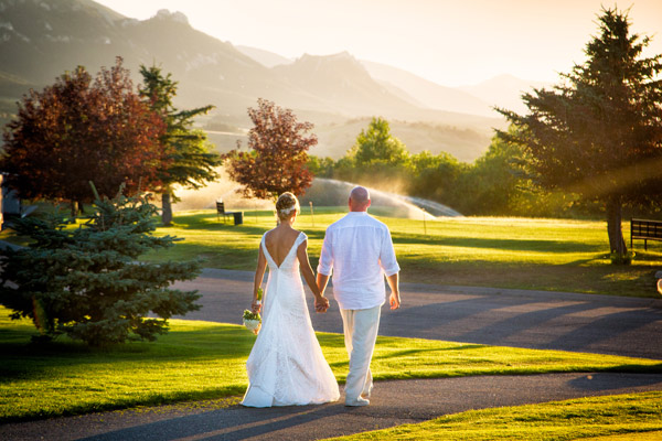 bride-and-groom-walking-into-sunset-at-red-lodge-mountain-weddings-montana